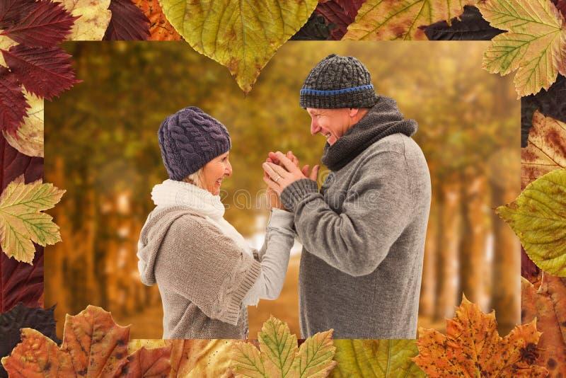 A imagem composta de pares maduros felizes no inverno veste o abraço fotos de stock