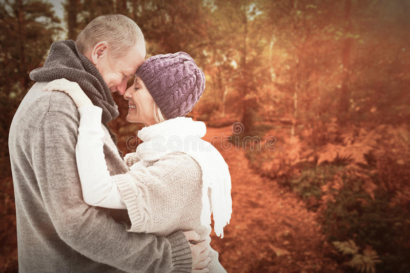 A imagem composta de pares maduros felizes no inverno veste o abraço imagem de stock