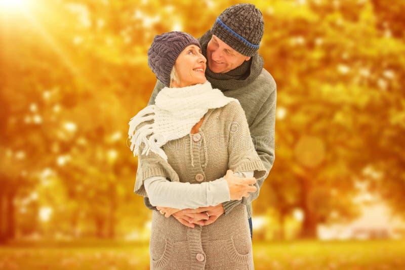 A imagem composta de pares maduros felizes no inverno veste o abraço foto de stock