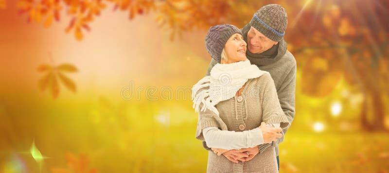 A imagem composta de pares maduros felizes no inverno veste o abraço fotografia de stock royalty free