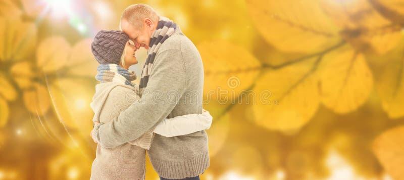 A imagem composta de pares maduros felizes no inverno veste o aperto imagens de stock