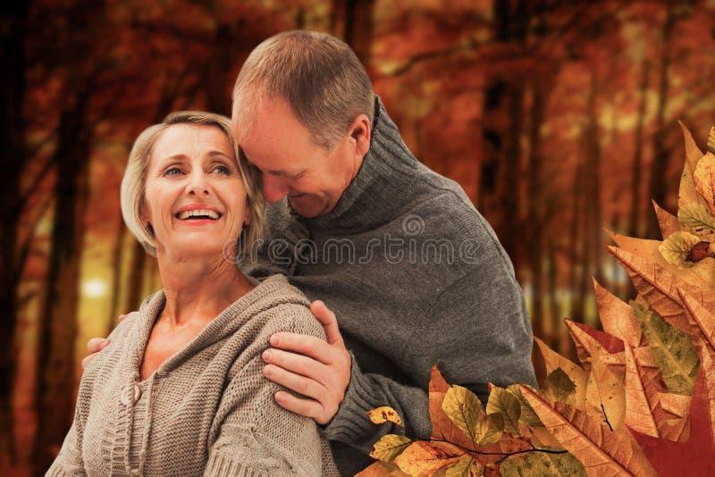 A imagem composta de pares maduros felizes no inverno veste-se fotografia de stock
