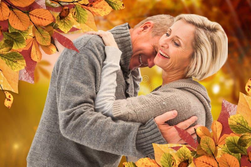 A imagem composta de pares maduros felizes no inverno veste-se imagens de stock royalty free