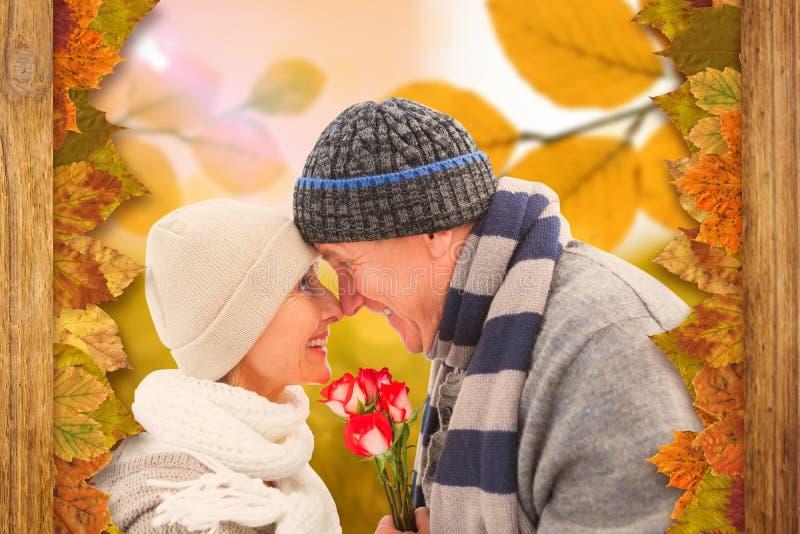 A imagem composta de pares maduros felizes no inverno veste-se com rosas foto de stock