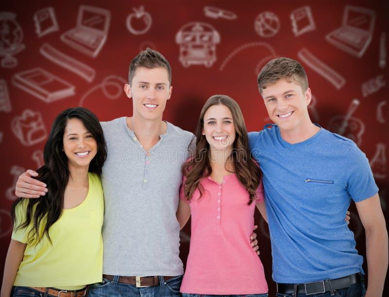Imagem composta de quatro amigos que sorriem e que abraçam-se como olham na câmera fotografia de stock