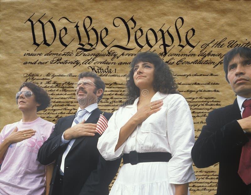 Imagem composta de quatro povos em uma cerimônia da cidadania sobreposta sobre o U S constitution fotos de stock