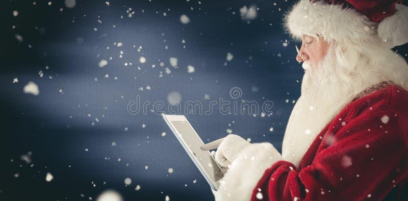 A imagem composta de Santa usa um PC da tabuleta imagem de stock