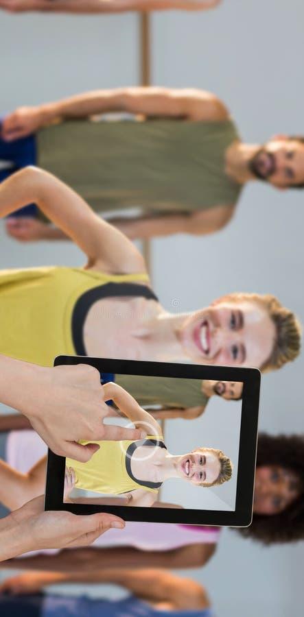 Imagem composta de tabuleta digital tocante das mãos contra o fundo branco imagem de stock