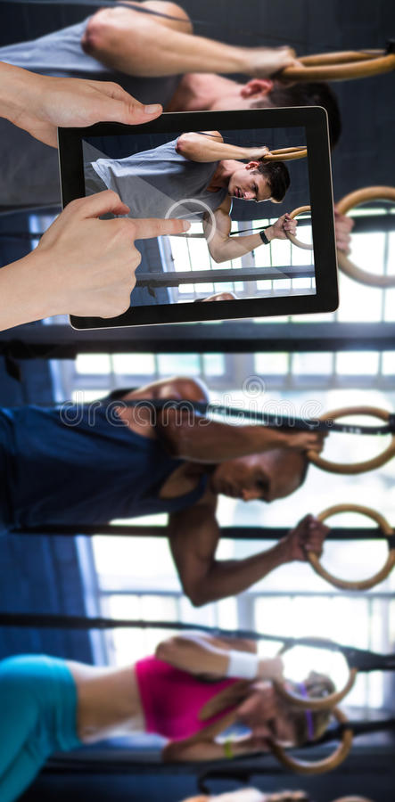 Imagem composta de tabuleta digital tocante das mãos contra o fundo branco fotografia de stock