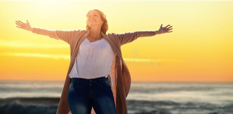 Imagem composta de um aumento da mulher seus braços acima fotos de stock royalty free