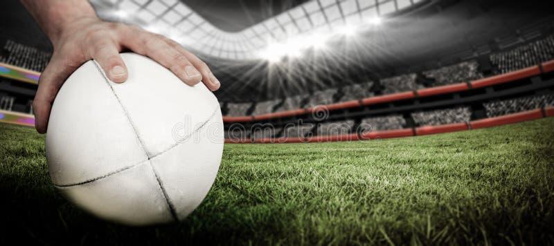 Imagem composta de um jogador do rugby que levanta uma bola de rugby fotografia de stock