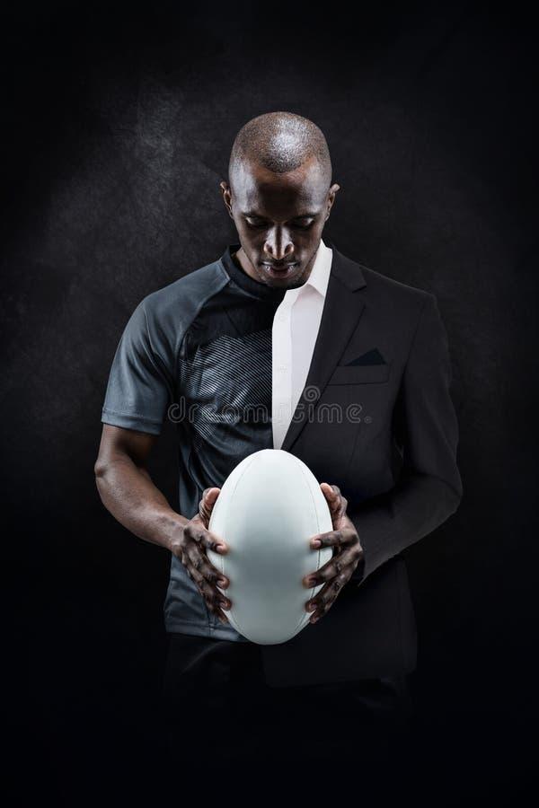 Imagem composta do atleta pensativo que olha a bola de rugby fotografia de stock royalty free