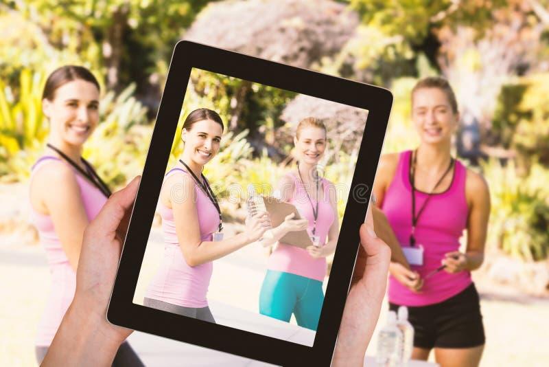 Imagem composta do close-up das mãos que guardam a tabuleta digital imagens de stock