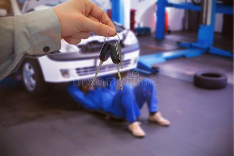 Imagem composta do concessionário automóvel que dá chaves a um cliente imagens de stock