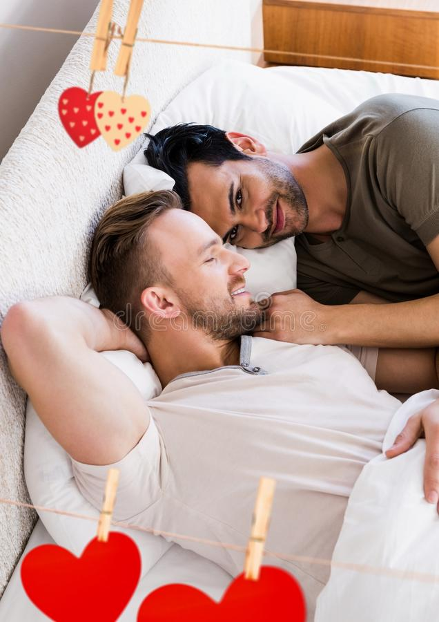 Imagem composta do coração de suspensão vermelho e dos pares homossexuais que encontram-se na cama fotos de stock royalty free