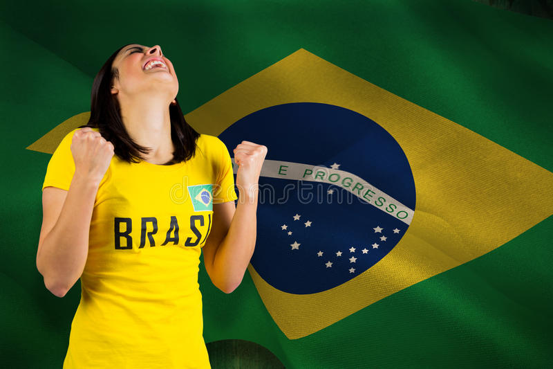 Imagem composta do fan de futebol entusiasmado no tshirt de Brasil imagem de stock royalty free