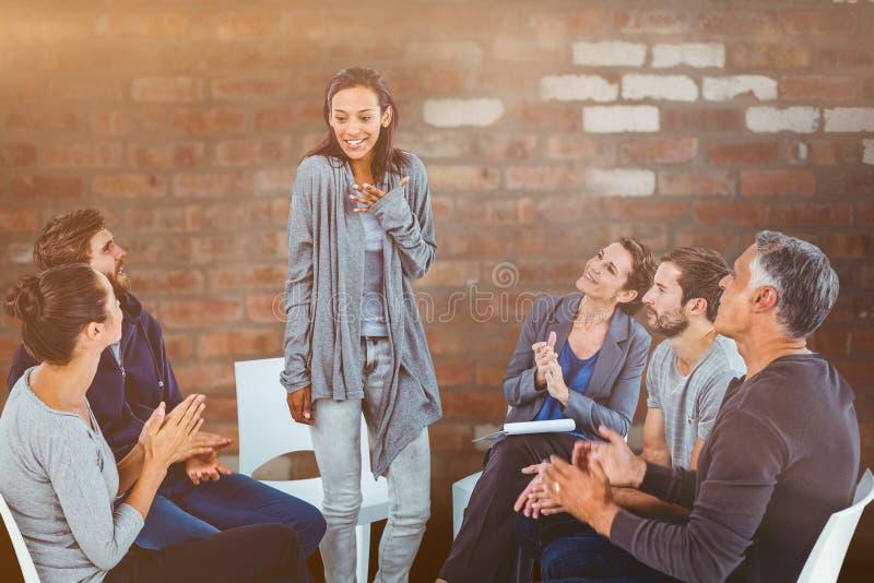 Imagem composta do grupo da reabilitação que aplaude a mulher deleitada que levanta-se foto de stock royalty free
