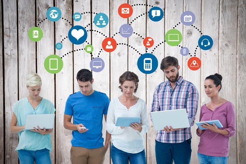 Imagem composta do grupo de colegas novos que usam o portátil e a tabuleta imagem de stock royalty free