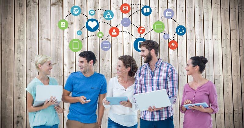 Imagem composta do grupo de colegas novos que usam o portátil e a tabuleta foto de stock