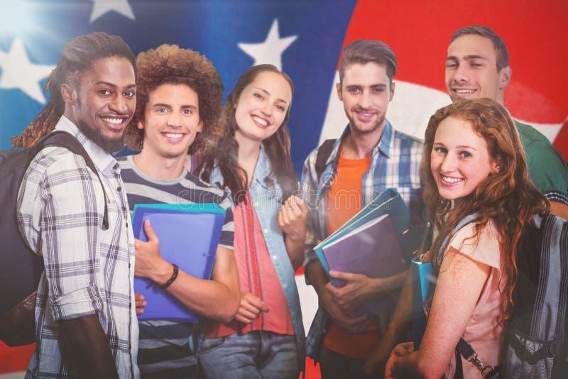 Imagem composta do grupo de sorriso de estudantes que guardam dobradores fotografia de stock royalty free