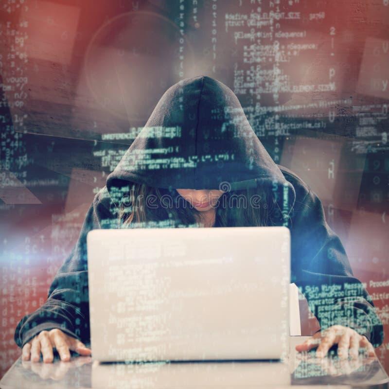 Imagem composta do hacker fêmea que senta-se pelo portátil na tabela foto de stock royalty free