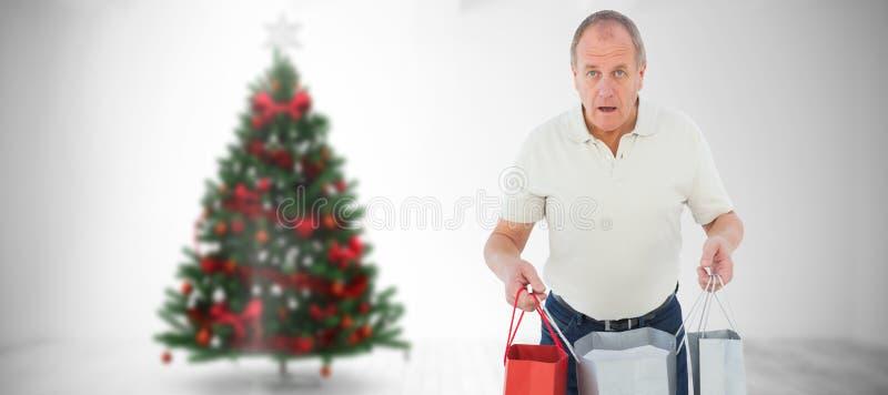 Imagem composta do homem chocado que guarda sacos de compras fotografia de stock