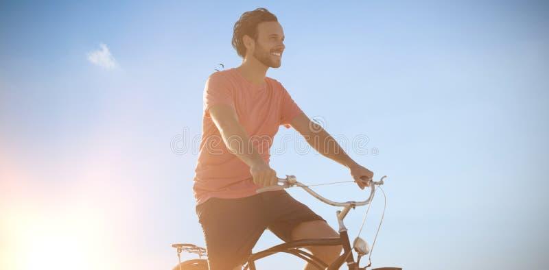 Imagem composta do homem considerável em um passeio da bicicleta em um dia ensolarado fotografia de stock royalty free