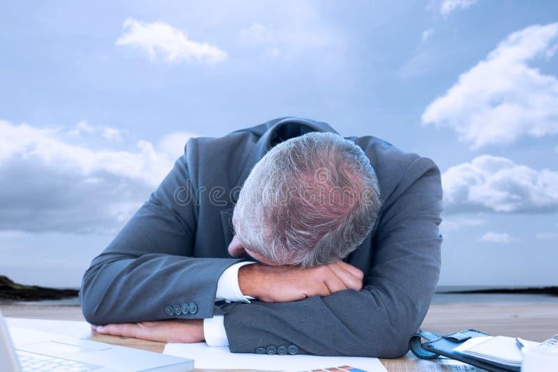 Imagem composta do homem de negócios cansado que descansa na mesa fotos de stock royalty free