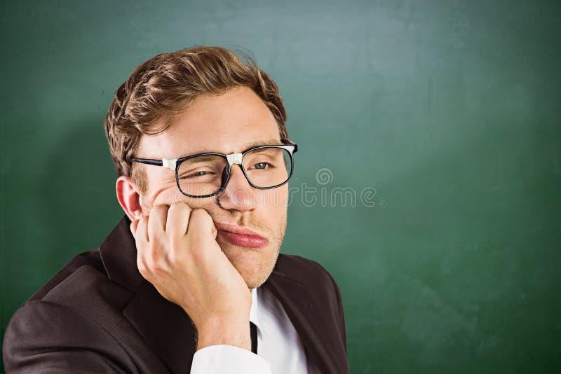 Imagem composta do homem de negócios geeky novo que olha furado fotografia de stock royalty free