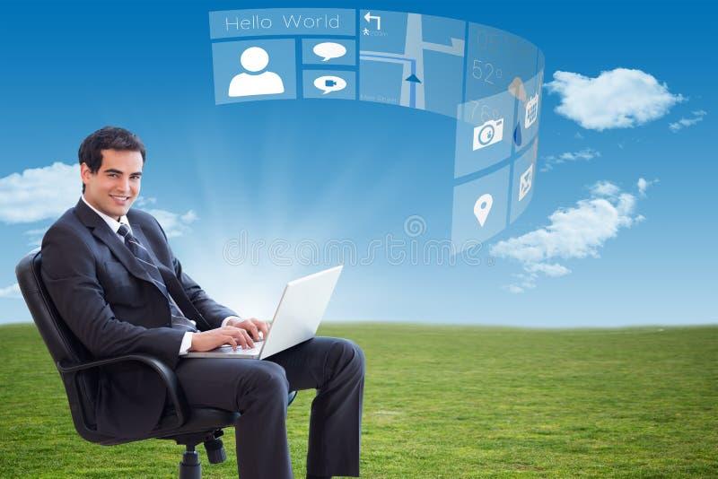 Imagem composta do homem de negócios novo que senta-se em uma poltrona que trabalha com um portátil imagens de stock