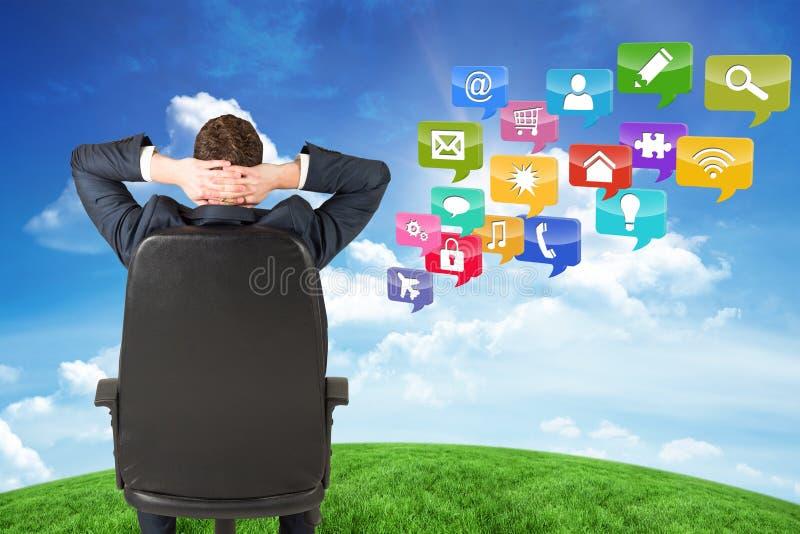 Imagem composta do homem de negócios que senta-se na cadeira de giro imagens de stock