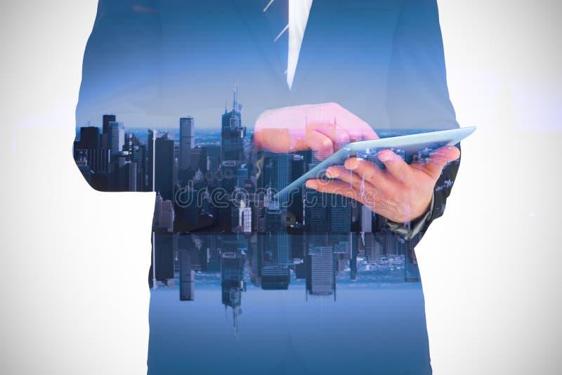Imagem composta do homem de negócios que toca em seu PC da tabuleta fotografia de stock