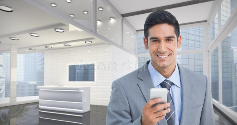 Imagem composta do homem de negócios que usa o telefone celular com colegas atrás fotografia de stock royalty free