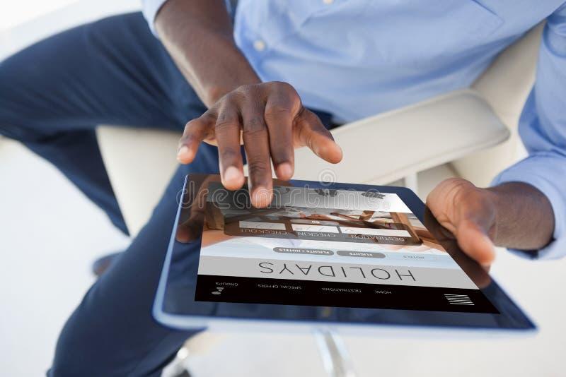 Imagem composta do homem de negócios que usa a tabuleta digital ao sentar-se na cadeira fotos de stock royalty free