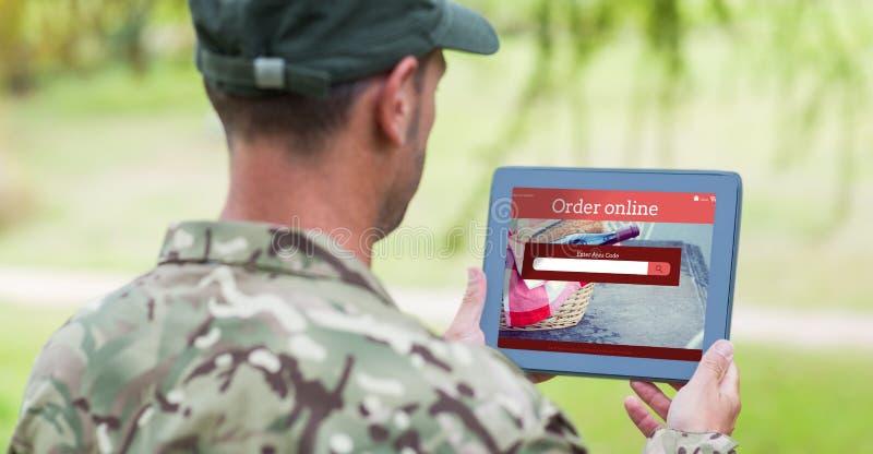 Imagem composta do homem do exército que usa a tabuleta imagem de stock royalty free