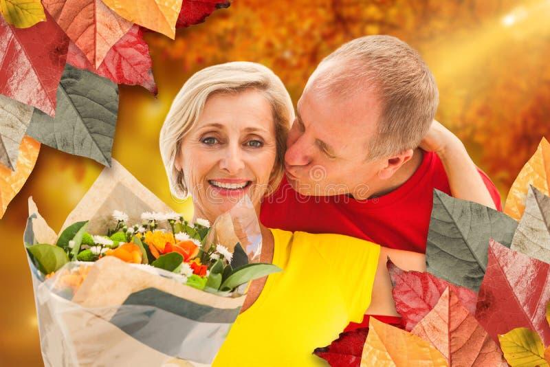 Imagem composta do homem maduro que beija seu sócio que guarda flores imagem de stock