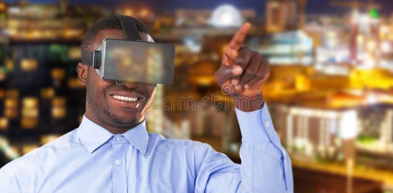 Imagem composta do homem que aponta ao vestir auriculares da realidade virtual contra a cidade iluminada imagem de stock royalty free