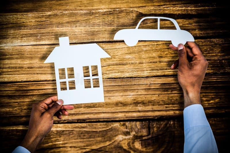 Imagem composta do homem que guarda um carro e uma casa no papel imagens de stock