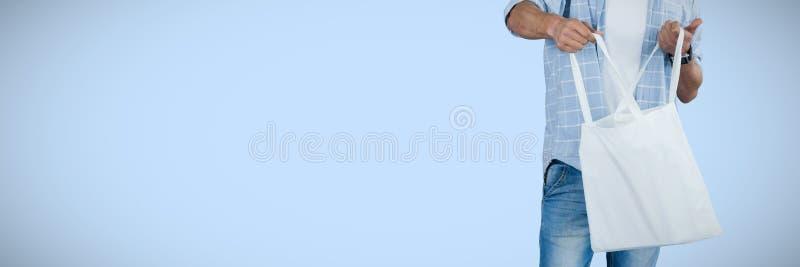 Imagem composta do homem que mantém o saco de compras contra o fundo branco fotos de stock