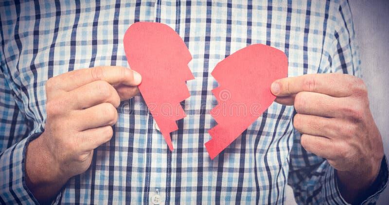 Imagem composta do homem triste com coração quebrado fotografia de stock royalty free
