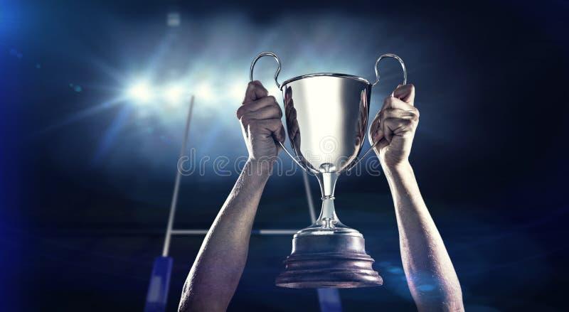 Imagem composta do jogador bem sucedido do rugby que guarda o troféu imagem de stock royalty free