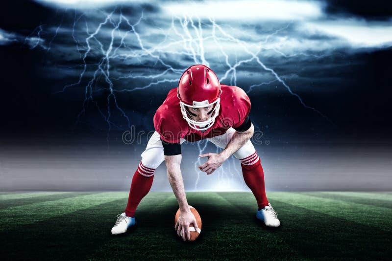 Imagem composta do jogador de futebol americano que começa o jogo de futebol 3d imagens de stock