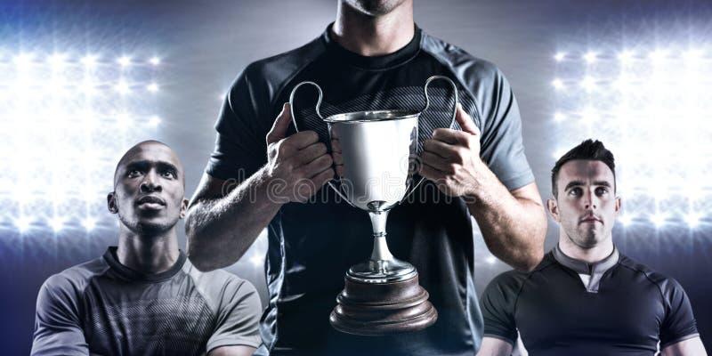 Imagem composta do jogador vitorioso do rugby que guarda o troféu foto de stock royalty free