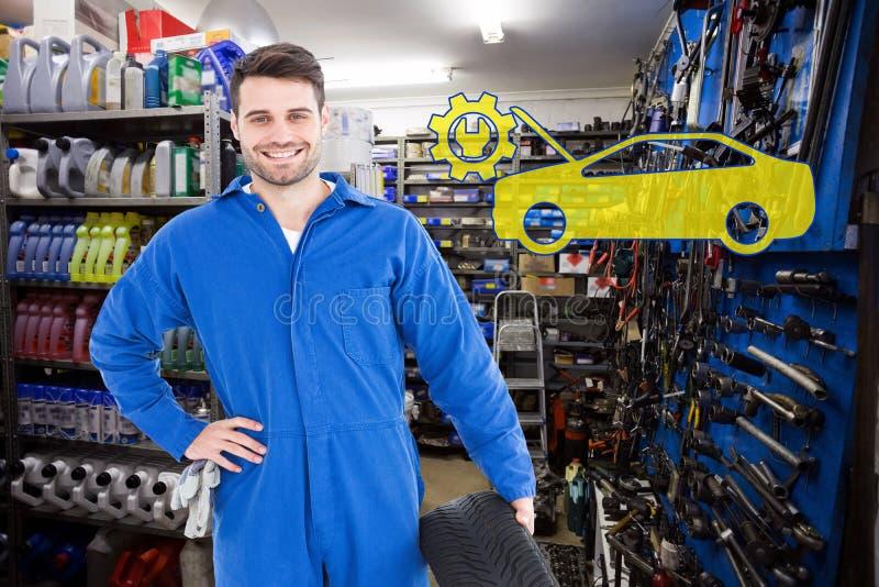 Imagem composta do mecânico masculino de sorriso que guarda o pneu foto de stock royalty free