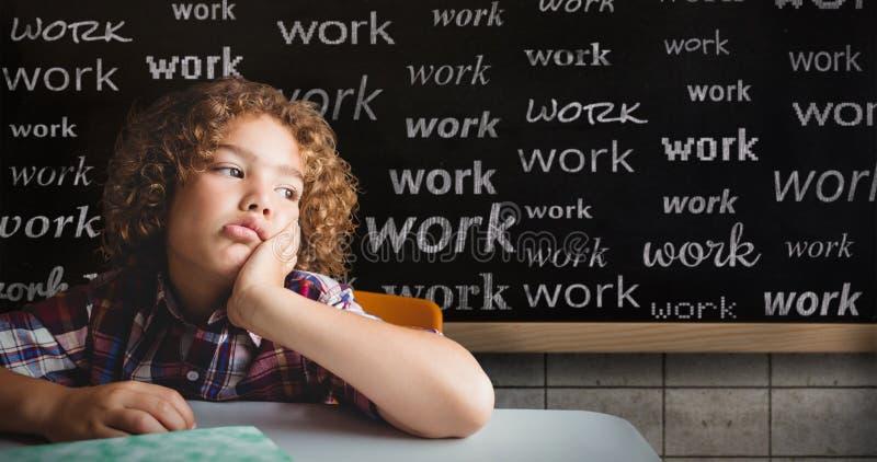 Imagem composta do menino de escola que senta-se em uma mesa imagens de stock