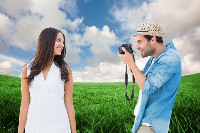 Imagem composta do moderno considerável que toma uma foto da amiga bonita fotografia de stock