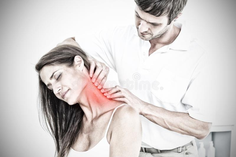 Imagem composta do quiroprático masculino que faz massagens o pescoço de uma jovem mulher imagem de stock