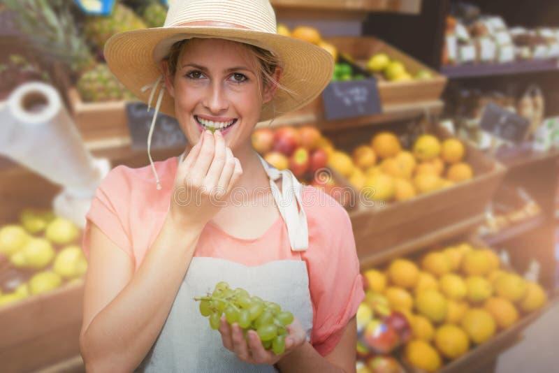 Imagem composta do retrato da jovem mulher de sorriso que come uvas fotografia de stock royalty free