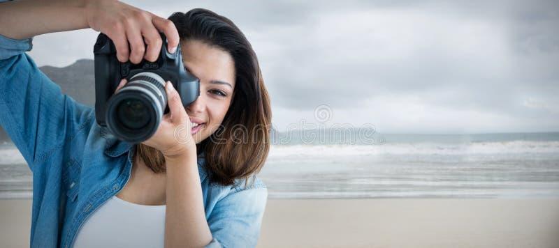 Imagem composta do retrato da jovem mulher que fotografa através da câmera imagem de stock