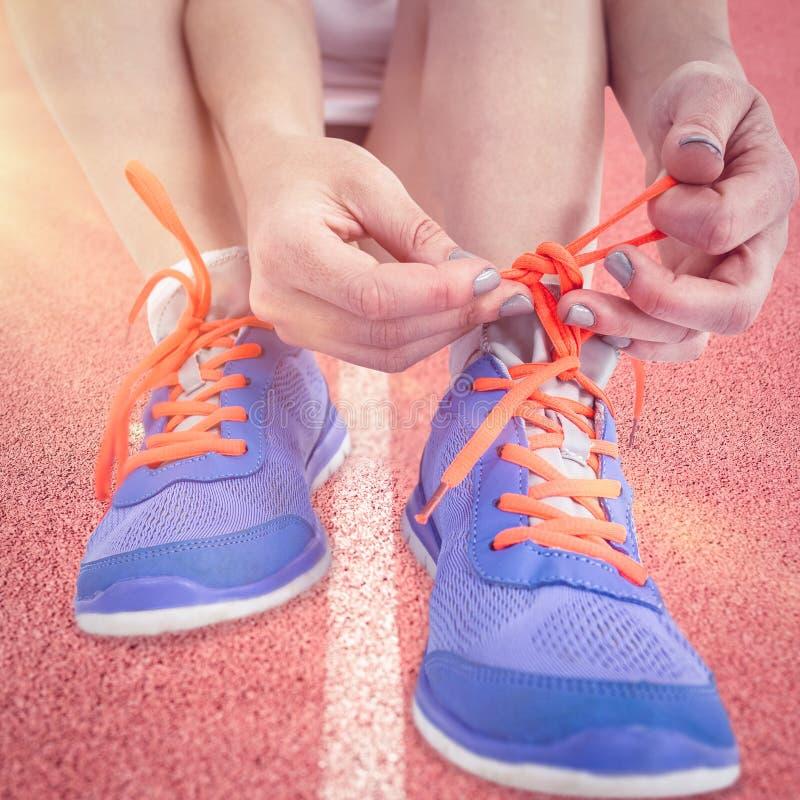 Imagem composta do retrato da mulher do atleta que amarra seus tênis de corrida fotos de stock